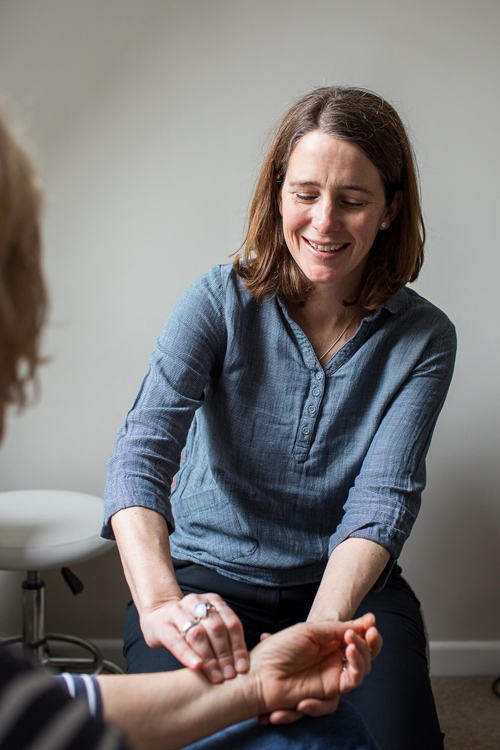Caiti Buck acupuncturist in Salisbury and Blandford, Dorset taking pulse of patient to aid diagnosis